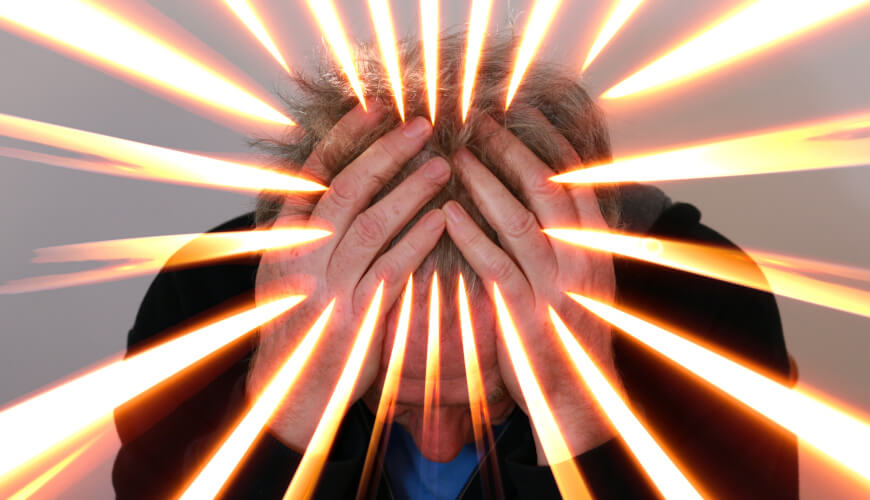 Man holding head with lights shooting out showing Migraine pain